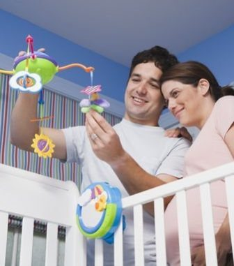Pregnant Hispanic Couple Holding Mobile Over Crib